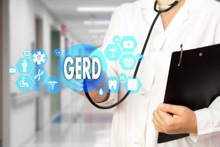 Medical Doctor with stethoscope and word GERD, Gastroesophageal reflux disease in Medical network