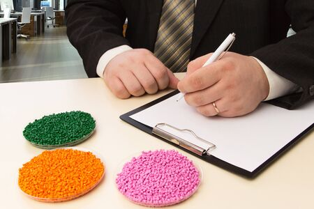 Businessman in the office signs a contract for the supply of plastic granules for industry. Reklamní fotografie