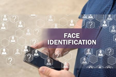 Biometric verification, face recognition technology.  Face identification Button on the touch screen with a blur background of the businessman with the phone.