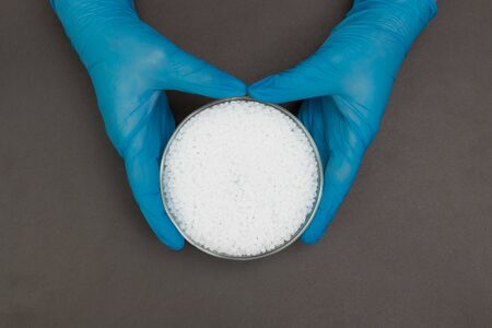 Plastic granules . Polypropylene, polyethylene pellets in hands with gloves. Quality control of plastic in the laboratory in production Stock fotó
