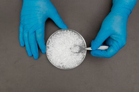 Plastic granules . Polyethylene pellets and hands with gloves. Quality control of plastic in the laboratory in production. BPA FREE.