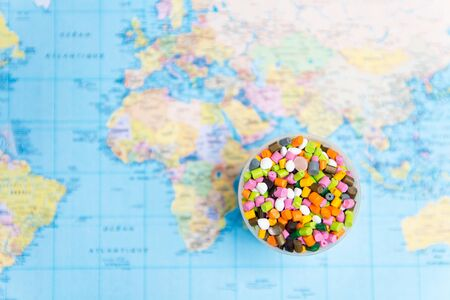 Plastic pellets on the background of the world map .The concept of Plastic pollution. The concept of world environment day.Selective focus