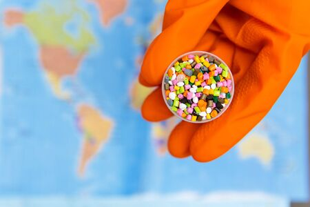 Plastic granules in hands with orange gloves on the background of the world map .The concept of Plastic pollution. Selective focus Stock fotó