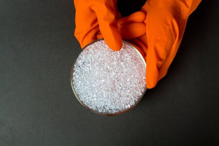 Plastic granules . Polyethylene pellets and hands with orange gloves. Quality control of plastic in the laboratory in production. BPA FREE.