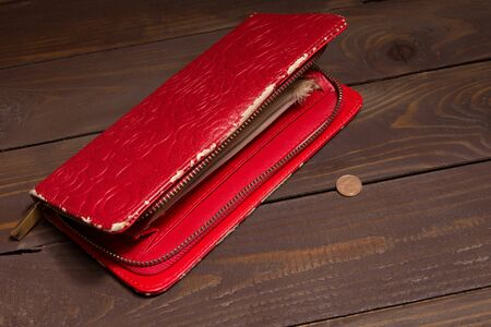 Old, worn out empty female red purse and 1 Euro cent on an empty wooden background. The concept of poverty, hunger