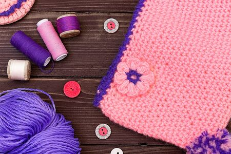 Knitted baby cap and Slippers, yarn for knitting on wooden table. The view from the top. Sewing accessories. 스톡 콘텐츠