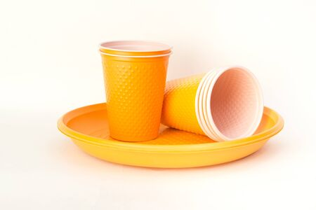 Plastic granules and disposable tableware made of polyethylene, polypropylene polymeric material on a white background. BPA FREE