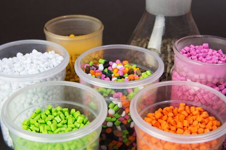 Plastic pellets. Dyes for plastic, polypropylene, polyethylene. Plastic granules in a measuring container and test tubes in the laboratory.