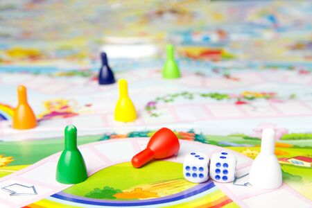 Board games for the home. Yellow, green, blue, red plastic chips and dice on Board games for children . Selective focus