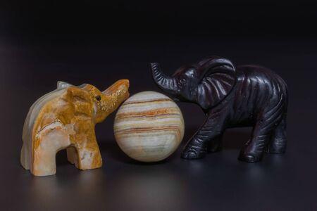 elephant figurines on a black background