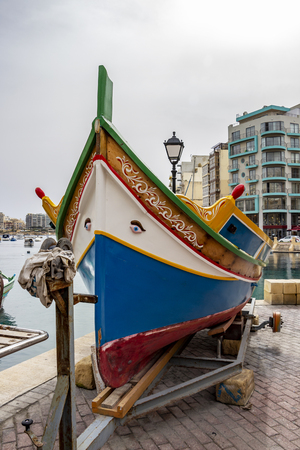 The bright colors of Luzzu - the traditional Maltese fishing boat pulled up on a boat ramp on shore in March at Spinola Bay, St. Julian's Malta