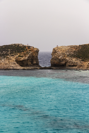 View from Comino to the Island of Cominotto with the crystal cyan Blue Lagoon Bay water, Malta