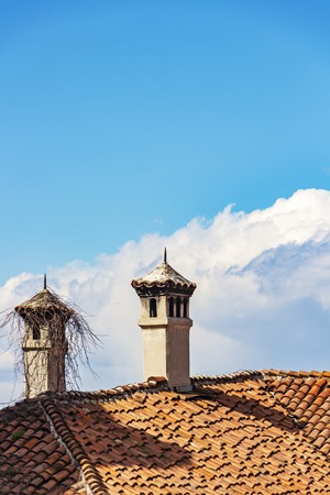 Two chimneys with beautiful tiled chimney caps on an old house rooftop against a Cumulus cloud in the sky at Plovdiv, Bulgaria