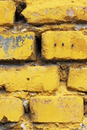 Close-up of a yellow painted brick wall of an old abandoned building with three nails in Sofia, Bulgaria texture background