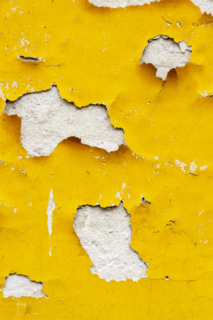 Old yellowish exterior wall coating of an old abandoned building in Sofia, Bulgaria chipping off, texture background