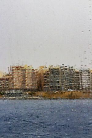 Vague Sliema cityscape seen through a wet ship's window on a rainy spring day at Sliema, Malta