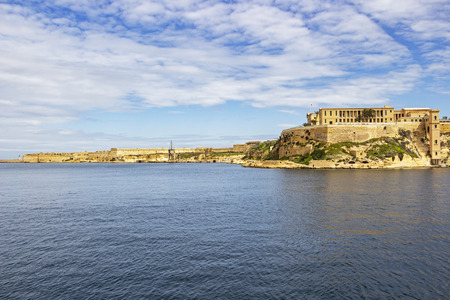 Scenic Mediterranean view of part of Bighi Hospital and Fort Ricasoli and St. Elmo breakwater lighthouse in the distance, at Grand Harbor, Malta