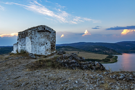 Exterior apse view of the medieval non-functioning Church of St. John Letni and part of the Pchelina Reservoir, Bulgaria on an August evening