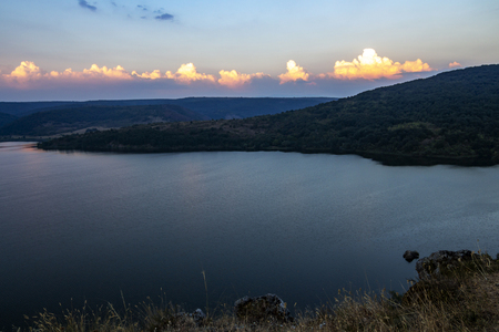 August sunset view to Pchelina Dam, Bulgaria with a row of sunlit clouds from the rocks next to the medieval non-functional Church of St. John Letni