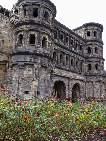 Porta Nigra - a Roman city gate in Trier - the oldest city in Germany with a rose alley in front, view from the main street Stock Photo