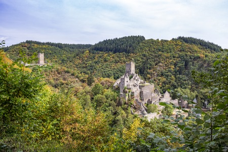 Autumn panoramic view to the ruins of Oberburg and Niederburg, the Upper and Lower Castle of Manderscheid, Germany as seen from the main street Stock Photo