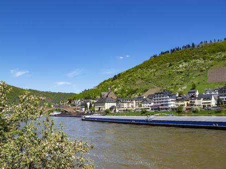 Picturesque view to Moselle River with a cargo ship at Cochem, Rhineland-Palatinate, Germany