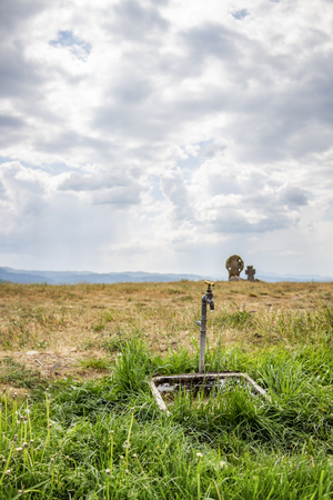 Exterior rural faucet dripping water in the foreground, two ancient stone crosses on a hill in the Bulgarian village of Chukovezer in the background, Dragoman Municipality, Sofia Province