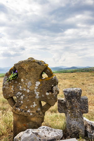 Flowers and coins as a religious offering on two ancient stone crosses on a hill in the Bulgarian village of Chukovezer, Dragoman Municipality, Sofia Province under dramatic sky Archivio Fotografico - 111306999