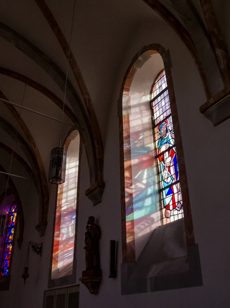 STEFFELN, GERMANY - MARCH 08, 2015: Stained glass windows and sunlight reflections at Saint Michael's Church in Steffeln, Rhineland-Palatinate, Germany Editorial