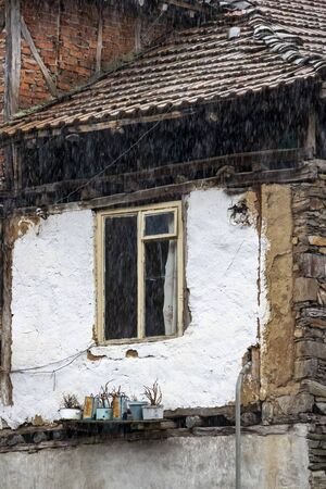 Window of an old poor house with plant pots in front in the village of Pirin in Pirin Mountains, Bulgaria, architectural detail, on a rainy March day