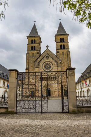Abbey's Basilica of St. Willibrord in Echternach, the oldest town in Luxembourg, exterior facade view under an overcast May sky