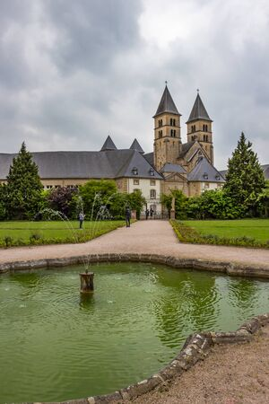 Overcast May view to the Abbey's Basilica of St. Willibrord in Echternach, Luxembourg from the abbey garden, the fountain in the foreground Stock Photo