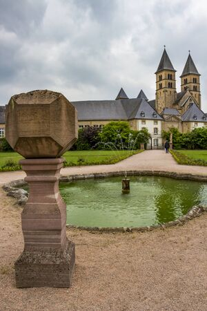 Abbey's Basilica of St. Willibrord in Echternach, Luxembourg under an overcast May sky in the background, a stone sundial and the fountain in the abbey garden in the foreground