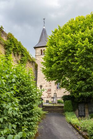 Summer overcast view of the main entrance to the Church of St. Peter in Roth an der Our, Germany - a former church of the Knights Templar, the church tower in the background Stock Photo