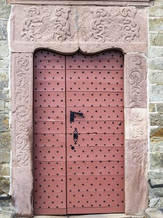 The beautiful old pinkish painted wooden door with metal rivets of St. Peters Church in the village of Beho, Belgium Фото со стока