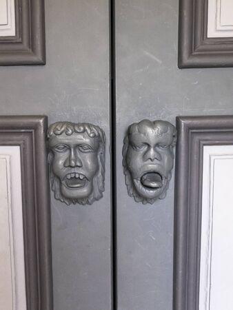 Doorknobs in the shape of grotesque masks, door of St. Peters Church in the village of Beho, Belgium