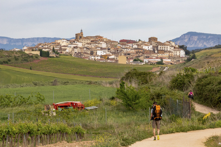 Rear view of two pilgrims on the Way of St. James, Camino de Santiago in Spain, the Cirauqui or Zirauki urban skyline in the distance