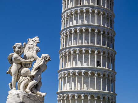 Leaning Tower of Pisa partial view and Putti Fountain sculpture in Piazza dei Miracoli or Square of Miracles in Pisa, Italy against a clear blue summer sky Stock Photo