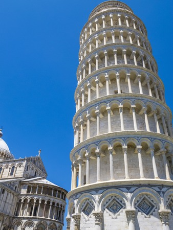 Summer clear blue sky close view of the Leaning Tower of Pisa and part of the Pisa Cathedral in Piazza dei Miracoli or Square of Miracles in Pisa, Italy