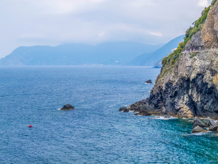 Mediterranean Sea and Cinque Terre National Park picturesque summer view with the Path of Love or Via dell'Amore in the distance, in Liguria, Italy