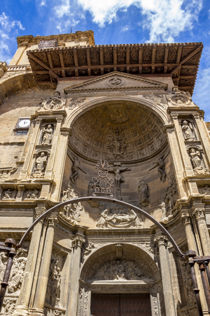 The Renaissance portal of the Church of Santa Maria in Viana, Navarre Spain against a beautiful blue May sky with fluffy white clouds