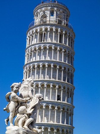 Leaning Tower of Pisa with Putti Fountain sculpture in the foreground in Piazza dei Miracoli or Square of Miracles in Pisa, Italy against a clear blue summer sky Stock Photo