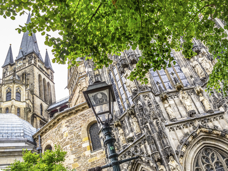 Aachen Cathedral exterior summer partial view behind green lime tree branches with a street lamp in the foreground, in Aachen, Germany 免版税图像