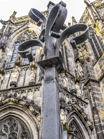Close-up of a wrought iron fence post, the Aachen Cathedral in the background, in Aachen, Germany