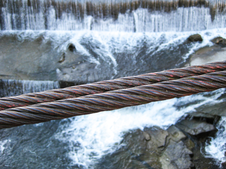 Close picture of a wire rope of an old Bulgarian suspension footbridge over Vidima River in the village of Debnevo, the blurred weir in the background