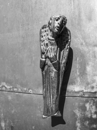 Door knob in the shape of an angel, entrance door of the Church of St. Lambert in Kalterherberg, Germany, black and white photography Archivio Fotografico