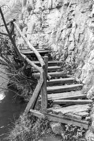 Elevated wooden walkway along Zlatna Panega River at Iskar-Panega Eco-path Geopark, the first geopark in Bulgaria, black and white photography