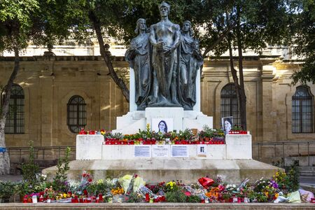 VALLETTA, MALTA - MARCH 06, 2018: Flowers, candles and tributes to Daphne Caruana Galizia at the foot of the Great Siege Monument