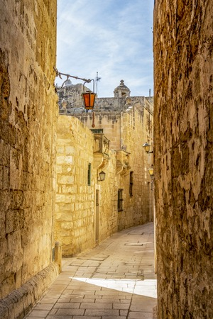 Sunny midday beautiful narrow typical limestone street with lanterns in Mdina - Citta Vecchia or Citta Notabile in Malta