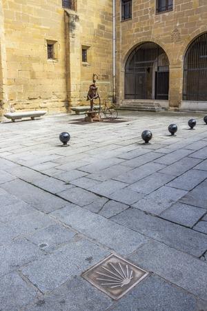 A marker in the pavement indicates the route of the Way of St. James, Camino de Santiago through Santo Domingo de la Calzada, La Rioja, Spain, a pilgrim fountain in the distance Stock Photo